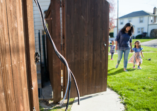 exposed downed power line with woman and child in background