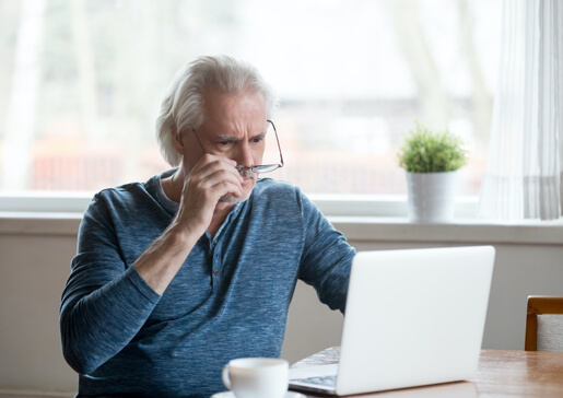 man looking at computer discerningly